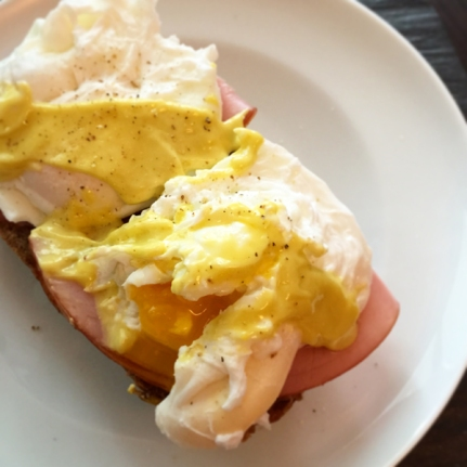 Homemade eggs benedict topped with garlic-lemon mayo